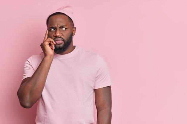 Horizontaal schot van intense ontevreden zwarte man met dikke baard houdt vinger op tempel diep in gedachten probeert zich iets in gedachten te herinneren, nonchalant gekleed geïsoleerd over roze muur