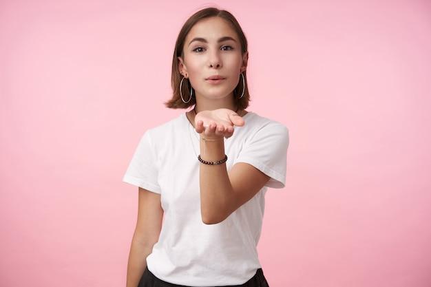 Horizontaal schot van jonge bruinogige brunette vrouw met bob kapsel lippen vouwen in de lucht kussen en haar hand opsteken terwijl ze over de roze muur in vrijetijdskleding staat
