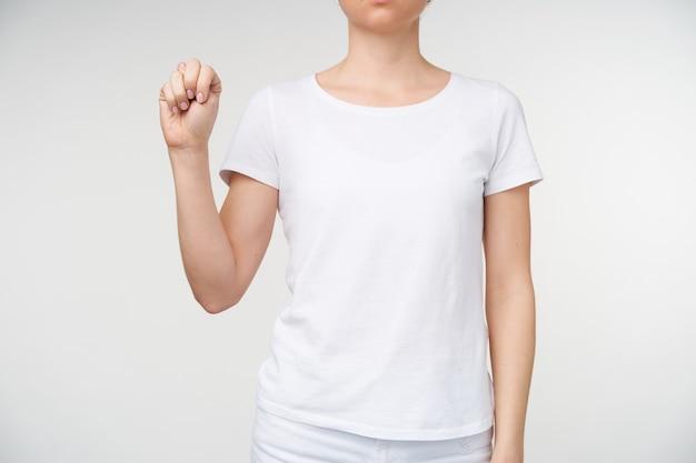 Horizontaal schot van jonge dame gekleed in vrijetijdskleding die hand omhoog houdt terwijl zij letter n toont met behulp van doof alfabet, staande op een witte achtergrond