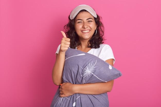 Horizontaal schot van jonge vrouw die hoofdkussen koestert en direct camera bekijkt die over roze wordt geïsoleerd