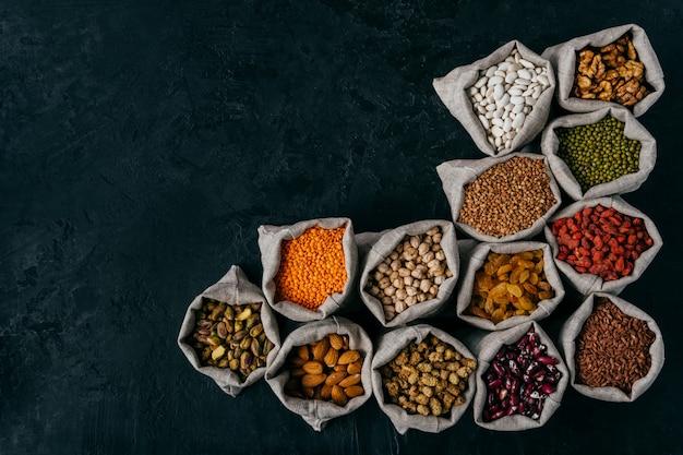 Horizontaal schot van kleine zakjes gevuld met amandelen, walnoten, rozijnen, garbanzo, bruine bonen, rode goji