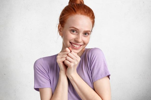 Horizontaal schot van knap vrouwelijk model met positieve uitdrukkingsmodellen in studio, drukt positieve emoties en gevoelens uit