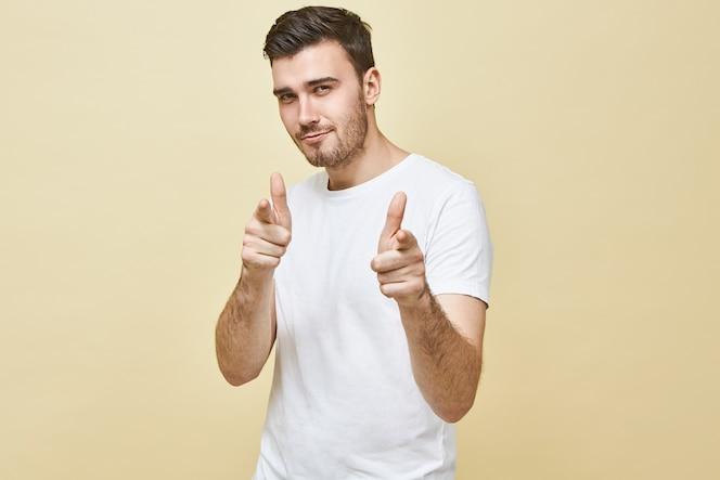 Horizontaal schot van knappe charismatische jonge man met zwart haar en stoppels poseren geïsoleerd wijzende vingers, met zelfverzekerde flirterige gezichtsuitdrukking, jou kiezen. lichaamstaal