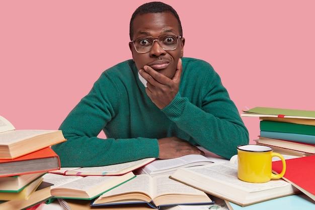 Horizontaal schot van knappe zwarte jonge man houdt kin, kijkt met nieuwsgierige uitdrukking, zoekt nuttige informatie in boeken, gekleed in groene trui