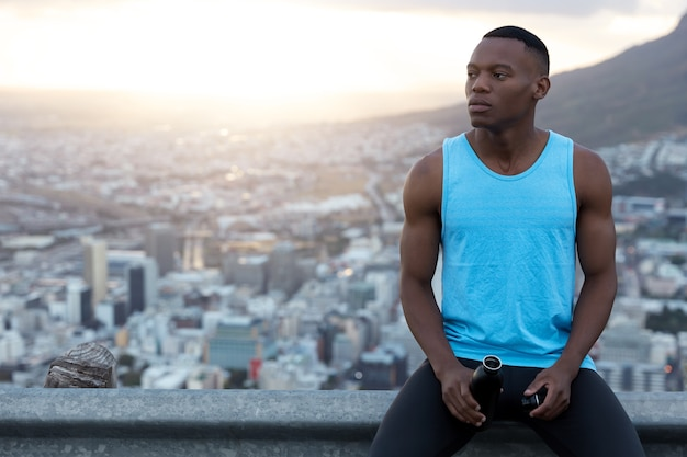 Horizontaal schot van knappe zwarte man in casual outfit, houdt fles water, diep in gedachten, rust boven stad met daglicht, heldere hemel met kopie ruimte voor uw promotie.