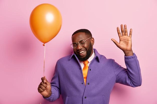 Horizontaal schot van knappe zwarte man met dikke haren, dansen op muziek, heeft plezier op partij houdt luchtballon