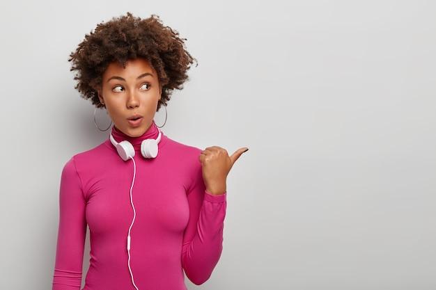 Horizontaal schot van krullende afro-amerikaanse vrouw met onder de indruk gezichtsuitdrukking