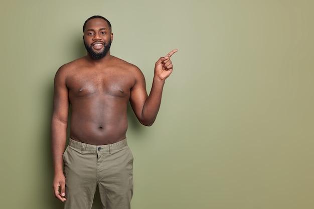 Horizontaal schot van lachende zwarte bebaarde man vormt met blote torso geeft aan op lege ruimte