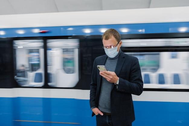 Horizontaal schot van mannelijke werknemer poseert op metroplatform, pendelt met openbaar vervoer, gebruikt moderne mobiele telefoon om route te controleren, draagt medisch beschermend masker tegen coronavirus of griep. gezondheidsrisico