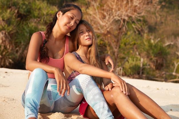 Horizontaal schot van moeder en dochter omhelzen op strand