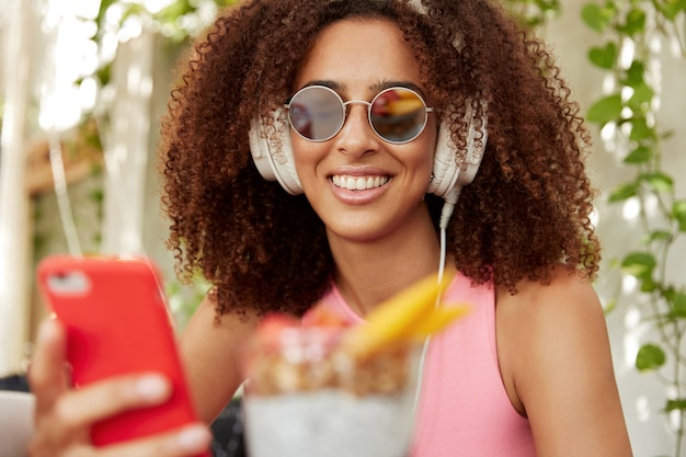 Horizontaal schot van mooi jong vrouwelijk model met donkere huid en krullend haar, draagt sunglaases, verbonden met hoofdtelefoons en slimme telefoon, luistert audiotrack. mensen en entertainment concept