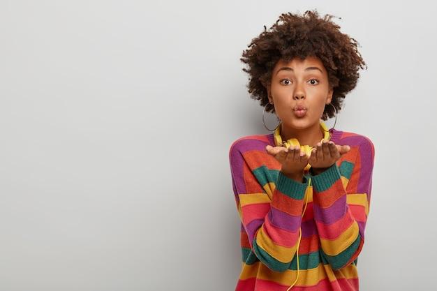 Horizontaal schot van mooie afro-amerikaanse vrouw zendt luchtkus, drukt liefde uit, maakt genegenheid valentijn gebaar, houdt lippen rond