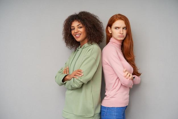 Horizontaal schot van mooie jonge vriendinnen met casual kapsel die verschillende emoties uitdrukken terwijl ze over grijze muur met gekruiste handen staan
