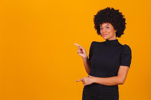 Horizontaal schot van mooie jonge vrolijke afro-amerikaanse vrouwelijke punten met voorvinger weg, geeft kopieerruimte aan op lege muur, geïsoleerd op gele achtergrond. bekijk dit eens. etniciteit concept