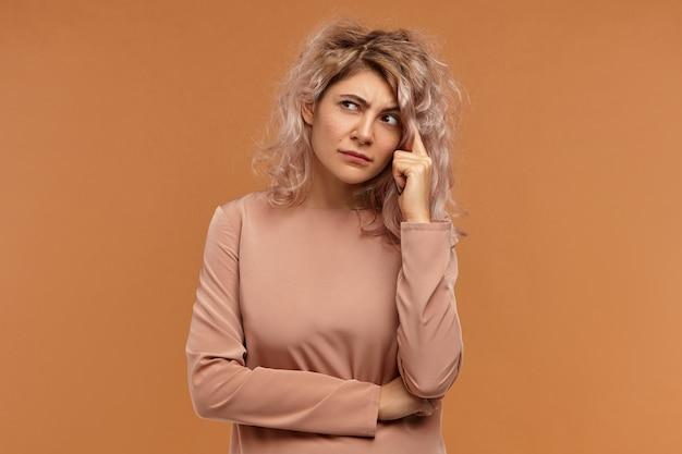 Horizontaal schot van mooie stijlvolle jonge europese vrouw met volumineus roze haar zijwaarts op zoek en hand op haar hoofd, iets na te denken