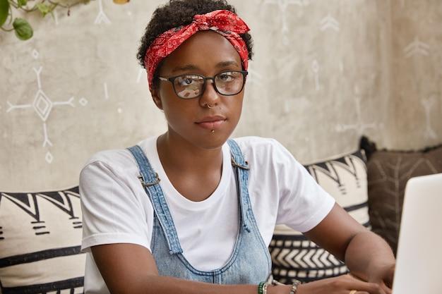 Horizontaal schot van mooie stijlvolle zwarte vrouw draagt een bril en rode hoofdband