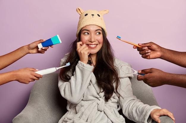 Horizontaal schot van mooie tevreden aziatische vrouw in zachte hoed en badjas