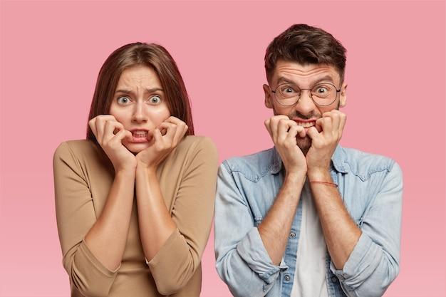 Horizontaal schot van nerveuze jonge vrouw en man bijten nagels met angstige uitdrukkingen