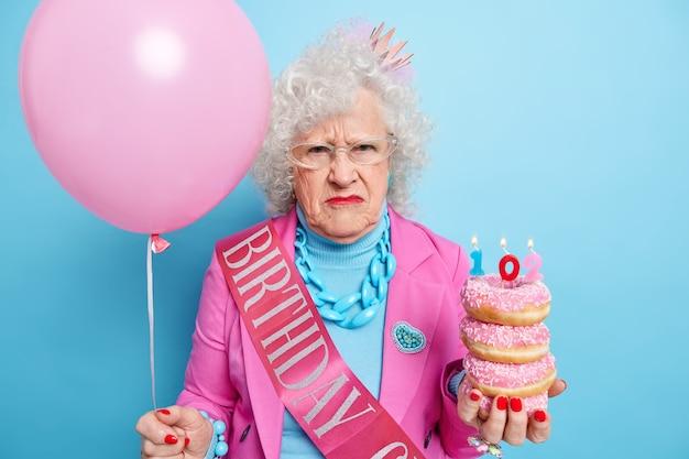 Horizontaal schot van ontevreden senior vrouw fronst gezicht heeft ongelukkige stemming houdt stapel smakelijke geglazuurde donuts met brandende kaars opgeblazen ballon
