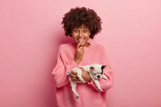 Horizontaal schot van opgetogen donkerhuidig meisje met krullend kapsel, heeft een nieuwsgierige vrolijke uitdrukking, houdt de vinger op de lippen, houdt kleine slaperige hond vast, modellen over roze muur. vriendschap en dieren
