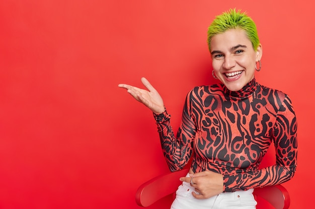 Horizontaal schot van positief trendy meisje dat betrokken is bij tienersubcultuur trekt je aandacht naar lege ruimte houdt handpalm omhoog toont reclame-inhoud draagt coltrui witte spijkerbroek geïsoleerd over rode muur