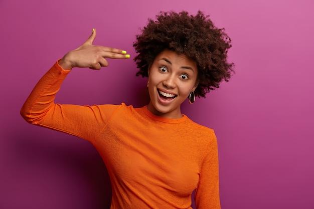 Horizontaal schot van positieve gekrulde vrouw schiet in tempels, maakt zelfmoordgebaar, dwazen rond, maakt vingerpistoolpistool, lacht vrolijk, draagt oranje trui, geïsoleerd op paarse muur