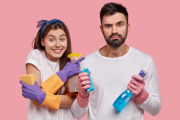 Horizontaal schot van positieve jonge vrouw wijst naar echtgenoot die geërgerde uitdrukking heeft, schoon huis samen, niet van vuil houdt