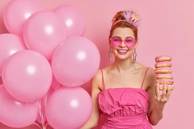 Horizontaal schot van positieve roodharige vrouw geniet van feestelijke gebeurtenis draagt roze zonnebril en stapel donuts houdt opgeblazen ballonnen geniet van verjaardagsfeestje