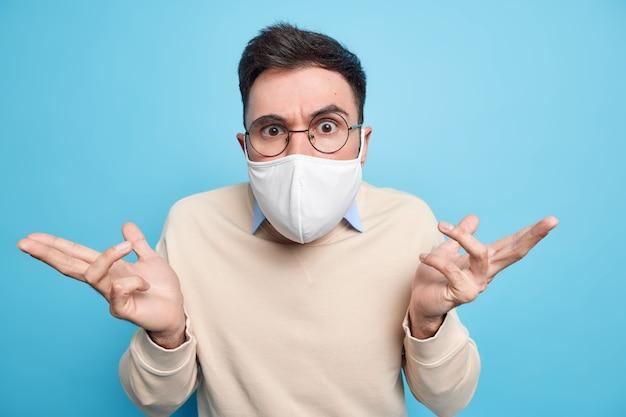 Horizontaal schot van serieuze man draagt ronde bril beschermend gezichtsmasker tegen coronavirusziekte verspreidt handen voelt zich verward kan geen keuze maken