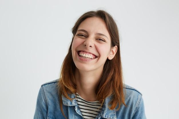 Horizontaal schot van speelse mooie jonge vrouw in goed humeur met vrolijke vrolijke blik, gelukkig lachend, genietend van een mooie dag. positieve menselijke emoties
