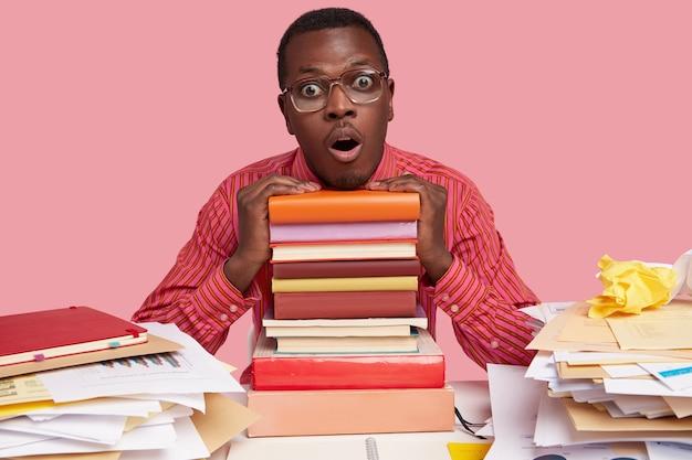 Horizontaal schot van stomverbaasde zwarte man heeft uitdrukking bang, houdt beide handen op schoolboeken