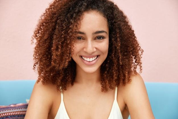 Horizontaal schot van tevreden aantrekkelijk jong vrouwelijk model met donker krullend haar, prettige glimlach op gezicht