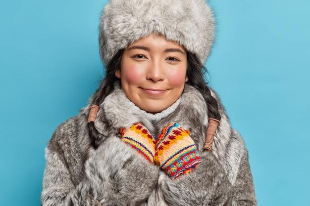 Horizontaal schot van tevreden aziatische vrouw kijkt gelukkig aan voorzijde draagt bontmuts en jas geniet van fantastische wintertijd geïsoleerd over blauwe muur