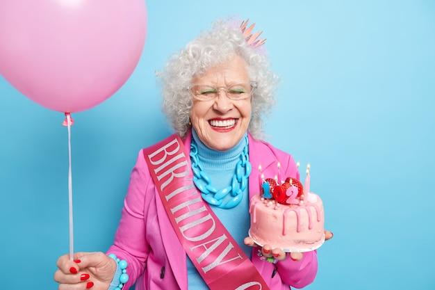 Horizontaal schot van tevreden senior vrouw lacht tandjes heeft een verzorgde blik viert 102e verjaardag geniet van vrolijk gezelschap ziet er mooi uit op oudere leeftijd houdt zoete cake en opgeblazen heliumballon