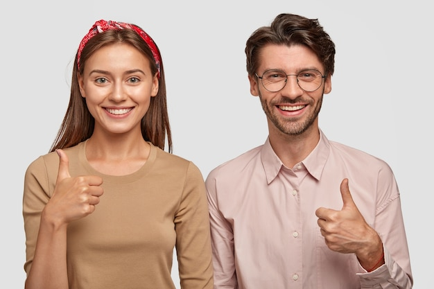 Horizontaal schot van tevreden tevreden vriendin en vriend steken duimen op