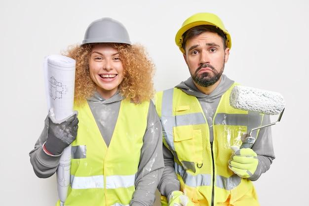 Horizontaal schot van twee professionele onderhoudsmedewerkers verf muren van nieuwbouw appartement vasthouden verfroller blauwdruk gebruiken gekleed in uniform verbouwt iets