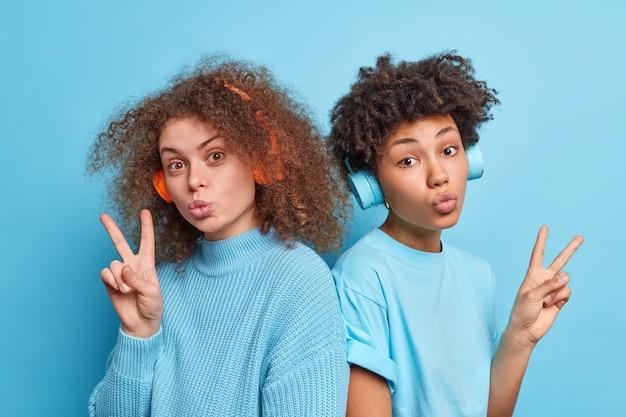 Horizontaal schot van twee vrouwelijke metgezellen met krullend haar houden de lippen gevouwen maak een vredesgebaar luister muziek via een koptelefoon ga naar elkaar toe geïsoleerd over blauwe muur genieten van vrije tijd.