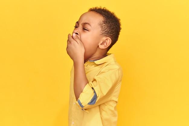 Horizontaal schot van uitgeputte slaperige afrikaanse schooljongen die geel overhemd draagt dat mond bedekt met hand geeuwend wordt moe na lange vermoeiende dag. verveling, slaap, bedtijd en beddengoed concept
