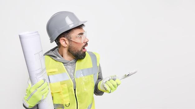 Horizontaal schot van verbijsterde mannelijke architect kijkt weg met geschokte uitdrukking houdt bouwgereedschap en blauwdruk controleert werk op bouwplaats poses tegen witte muur kopieerruimte