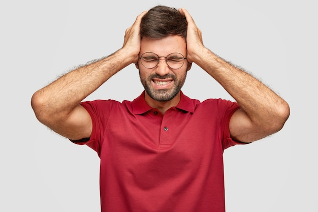 Horizontaal schot van vermoeidheid jonge euroepean ongeschoren man houdt handen op het hoofd, voelt zich uitgeput na het werk op kantoor, heeft hoofdpijn, draagt casual felrood t-shirt, geïsoleerd over witte muur