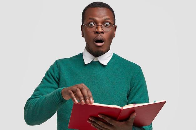 Horizontaal schot van verrast bang zwarte man staart met gepofte ogen, boek leest