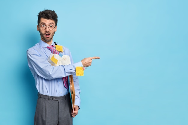 Horizontaal schot van verrast intelligente mannelijke student omringd met papieren gekleed in formele kleding geeft opstartideeën punten weg op kopie ruimte