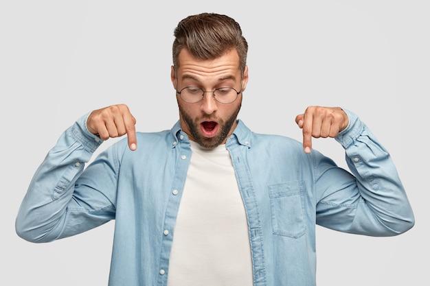 Horizontaal schot van verrast ongeschoren jonge man wijst naar beneden, opent mond wijd, ziet iets verbluffends op de vloer, draagt een stijlvol shirt, geïsoleerd over een witte muur. mensen en emoties concept
