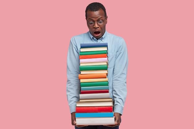 Horizontaal schot van verraste donkere student met hoop handboeken, staart met verbazing