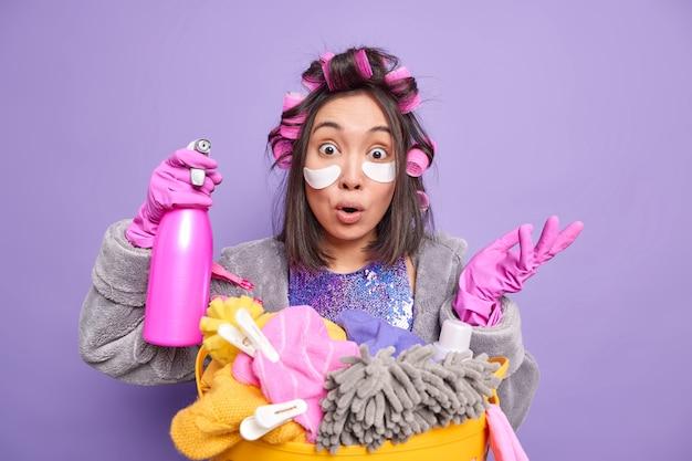 Horizontaal schot van verraste huisvrouw haalt schouders op, handpalm houdt wasmiddel vast, kan geen slimme reinigingsoplossing vinden, doet wasgoed past haarkrulspelden toe schoonheidspads geïsoleerd over paarse achtergrond