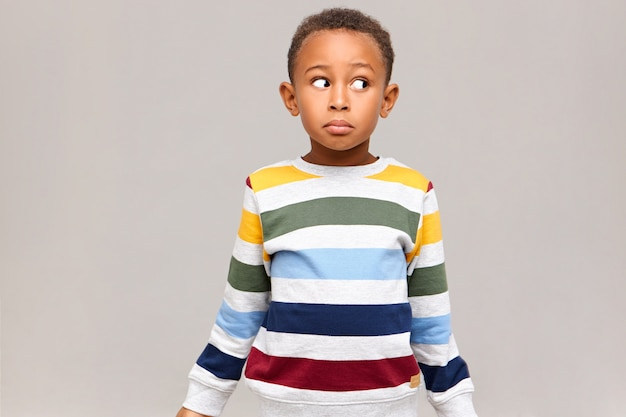 Horizontaal schot van verwarde grappige afro-amerikaanse jongen in gestreepte trui wegkijken met clueless gezichtsuitdrukking, schuldig voelen omdat hij alle snoep at, deed alsof hij onschuldig was. ik weet het niet