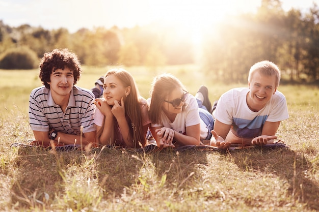 Horizontaal schot van vier gelukkige vrienden liggen op de grond, picknicken tijdens zonnige zomerdag, hebben positieve uitdrukkingen, glimlachen aangenaam naar de camera. grappige metgezellen die graag hun vrije tijd samen doorbrengen