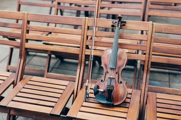Horizontaal schot van viool op houten stoel met boog. muziekinstrumenten concept.