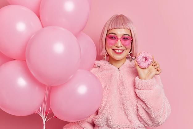 Horizontaal schot van vrij aziatische vrouw heeft een aangename glimlach op het gezicht houdt heerlijke donut opgeblazen ballonnen glimlach graag poses binnen