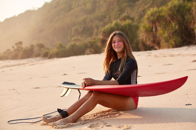 Horizontaal schot van vrij glimlachend jong meisje met surfzink op gezicht, voelt ontspannen wit aan zandstrand zit